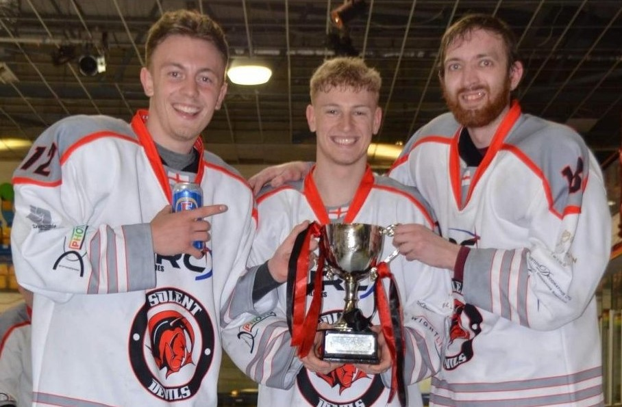 Solent Devils' IW players, from left: Dan Shier, Alex Trendall and Kieran Annis, with the NIHL Division 2 play off trophy, need help with travel expense to continue playing for the team.